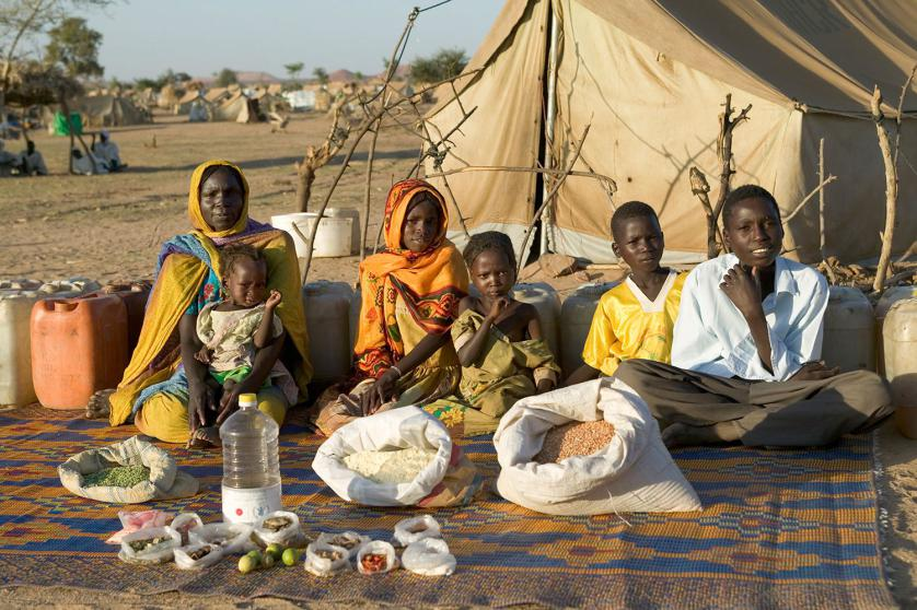 CHA104.0001.xxf1rw (MODEL RELEASED IMAGE) The Aboubakar family of Darfur province, Sudan, in front of their tent in the Breidjing Refugee Camp, in eastern Chad, with a week's worth of food. D'jimia Ishakh Souleymane, 40, holds her daughter Hawa, 2; the other children are (left to right) Acha, 12, Mariam, 5, Youssouf, 8, and Abdel Kerim, 16. Cooking method: wood fire. Food preservation: natural drying. Favorite food—D'jimia: soup with fresh sheep meat. /// The Aboubakar family is one of the thirty families featured in the book Hungry Planet: What the World Eats (p. 56). Food expenditure for one week: $1.23 USD. (Please refer to Hungry Planet book p. 57 for the family's detailed food list.)