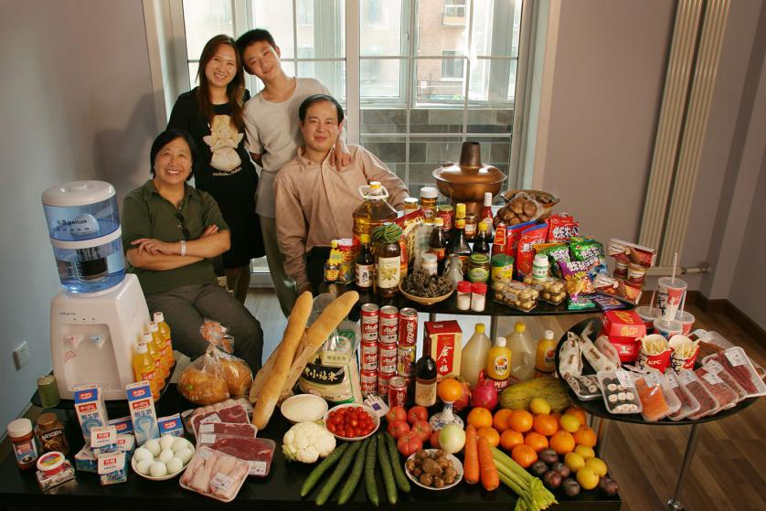 CHI103.0001.xxf1rw (MODEL RELEASED IMAGE) The Dong family in the living room of their one-bedroom apartment in Beijing, China, with a week's worth of food. Seated by the table are Dong Li, 39, and his mother, Zhang Liying, 58, who eats with them a few times a week. Behind them stand Li's wife, Guo Yongmei, 38, and their son, Dong Yan, 13. Cooking method: gas stove. Food preservation: refrigerator-freezer. Favorite food—Dong Yan: yuxiang rousi—fried shredded pork with sweet and sour sauce. /// The Dong family is one of the thirty families featured in the book Hungry Planet: What the World Eats (p. 74). Food expenditure for one week: $155.06 USD. (Please refer to Hungry Planet book p. 75 for the family's detailed food list.)