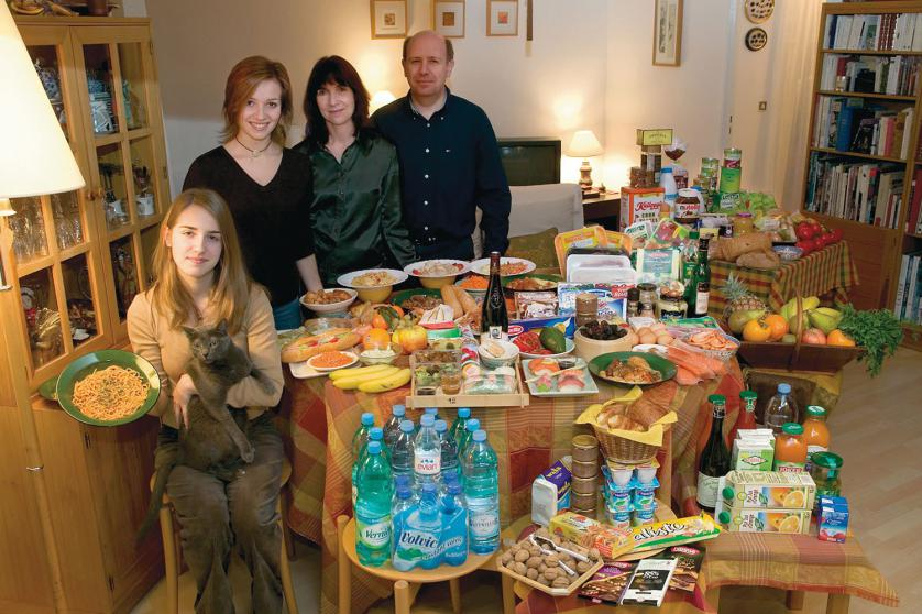 FRA04.0001.xxf1rw (MODEL RELEASED IMAGE) The Le Moine family in the living room of their apartment in the Paris suburb of Montreuil, with a week's worth of food. Michel Le Moine, 50, and Eve Le Moine, 50, stand behind their daughters, Delphine, 20 (standing), and Laetitia, 16 (holding spaghetti and Coppelius the cat). Cooking methods: electric stove, microwave oven. Food preservation: refrigerator-freezer. Favorite foods—Eve: fresh vegetables. Delphine: Thai food. Laetitia: pasta carbonara. /// The Le Moine family is one of the thirty families featured in the book Hungry Planet: What the World Eats (p. 124). Food expenditure for one week: $419.95 USD. (Please refer to Hungry Planet book p. 125 for the detailed food list.)