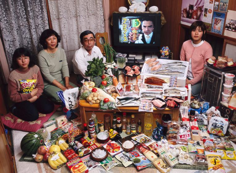 JAP01.0001.xxf1s (MODEL RELEASED IMAGE) The Ukita family—Sayo Ukita, 51, and her husband, Kazuo Ukita, 53, with children Maya, 14 (holding chips) and Mio, 17—in their dining room in Kodaira City, Japan, with one week's worth of food. Cooking methods: gas stove, rice cooker. Food preservation: small refrigerator-freezer. Favorite foods—Kazuo: sashimi. Sayo: fruit. Mio: cake. Maya: potato chips. /// The Ukita family is one of the thirty families featured in the book Hungry Planet: What the World Eats (p. 180). Food expenditure for one week: $317.25 USD. (Please refer to Hungry Planet book p. 181 for the family's detailed food list.)