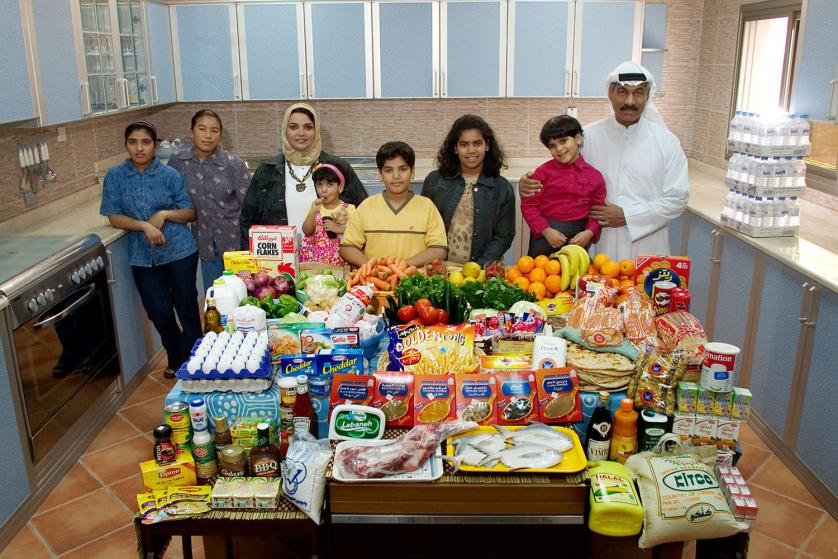 KUW03.0001.xxf1rw (MODEL RELEASED IMAGE) The Al Haggan family and their two Nepali servants in the kitchen of their home in Kuwait City, Kuwait, with one week's worth of food. Standing between Wafaa Abdul Aziz Al Qadini, 37 (beige scarf), and Saleh Hamad Al Haggan, 42, are their children, Rayyan, 2, Hamad, 10, Fatema, 13, and Dana, 4. In the corner are the servants, Andera Bhattrai, 23 (left), and Daki Serba, 27. Cooking methods: gas stoves (2), microwave. Food preservation: refrigerator-freezer. /// The Al Haggan family is one of the thirty families featured in the book Hungry Planet: What the World Eats (p. 196). Food expenditure for one week: $221.45 USD. (Please refer to Hungry Planet book p. 197 for the family's detailed food list.)