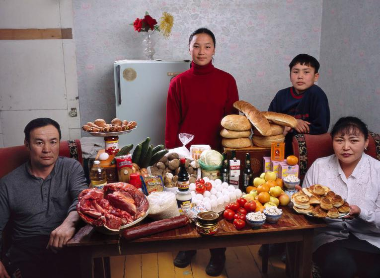 MON01.0001.xxf1s (MODEL RELEASED IMAGE) The Batsuuri family in their single-room home—a sublet in a bigger apartment—in Ulaanbaatar, Mongolia, with a week's worth of food. Standing behind Regzen Batsuuri, 44 (left), and Oyuntsetseg (Oyuna) Lhakamsuren, 38, are their children, Khorloo, 17, and Batbileg, 13. Cooking methods: electric stove, coal stove. Food preservation: refrigerator-freezer (shared, like the stoves, with two other families). /// The Batsuuri family is one of the thirty families featured in the book Hungry Planet: What the World Eats (p. 226). Food expenditure for one week: $40.02 USD. (Please refer to Hungry Planet book p. 227 for the family's detailed food list.)